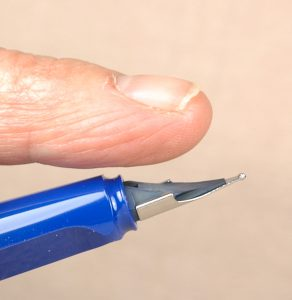 Place your index finger on the inkfeed to stabilize and support the fragile feed when you change a nib.