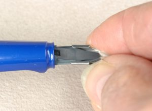Turn the inkfeed upside down where you can see the tracks for the runners of the nib to slide into place. Gently pinch the side of the Lamy replacement nib and slowly slide or wiggle the nib into place.